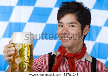 Asian Boy is holding a full Oktoberfest beer stein and smiles happy in camera. Isolated on white. - stock photo