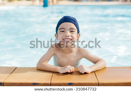 Asian boy is laughing on the pool, boy swimming and playing in water in swimming pool - stock photo