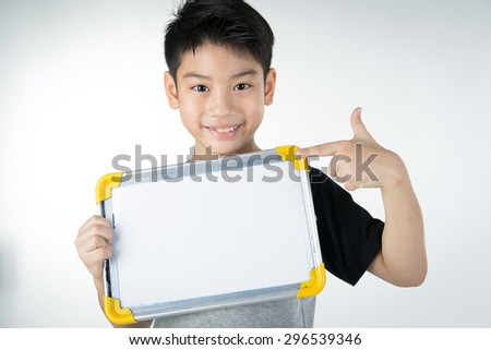 Asian boy is little smile with blank white board and looking camera on gray background - stock photo