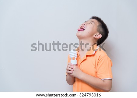 Asian boy joking gesture licking fake ice cream made with energy saving lamp, concept idea, on grey wall background with soft shadow - stock photo