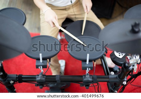 Asian boy learning play electronic drum in music room - stock photo