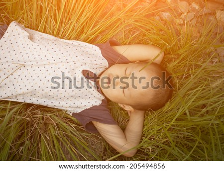 Asian boy lying on the grass in sunset
