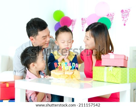 Asian boy make a wish on his birthday party - stock photo