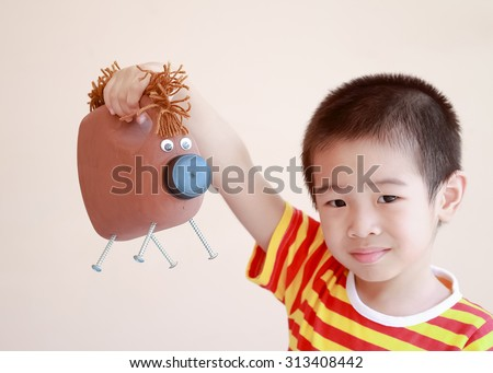 Asian boy making a horse from reuse bottle - stock photo