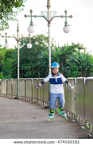 Asian boy on roller skates in the park.