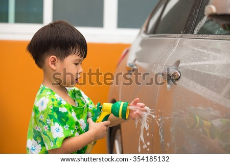 asian boy play with water spray