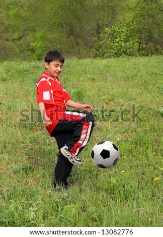 asian boy playing football on green grass - stock photo