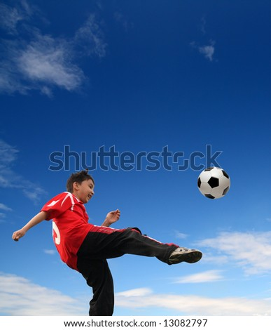asian boy playing football under blue sky