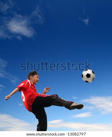 asian boy playing football under blue sky - stock photo