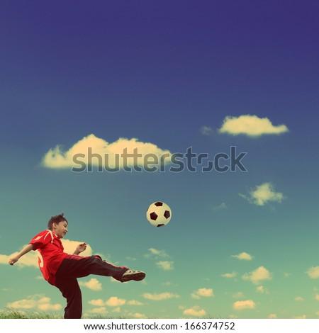 asian boy playing football under blue sky - vintage retro style - stock photo