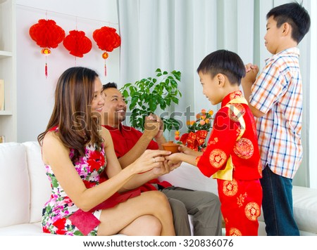 Asian boy presenting tea to his mother during chinese new year - stock photo