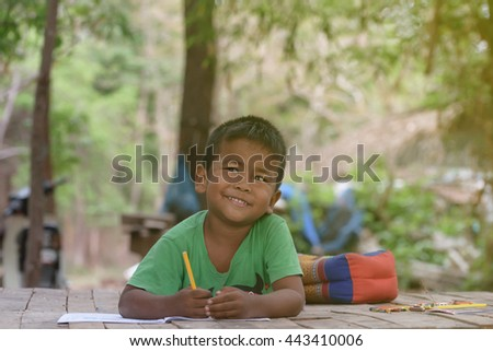 Asian boy reading a book happily.