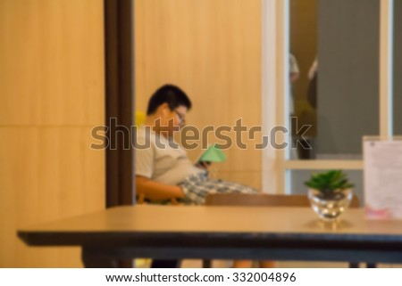 asian boy reading a book in library ,blurry background