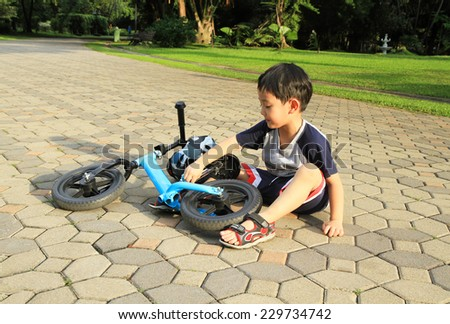 Asian boy sitting near his bicycle in the park - stock photo