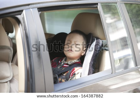 asian boy sleep in car with safety belt