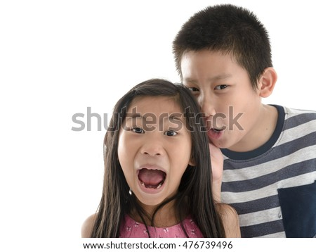 Asian boy telling girl a secret on white background with copyspace. Girl with surprising face and open her mouth