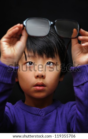 Asian boy with bad eyesight trying his new glasses - stock photo
