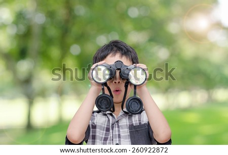 Asian boy with binoculars in garden - stock photo