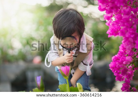 Asian boy with magnifying glass outdoors - stock photo