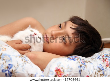 asian boy with white cat in bed - stock photo