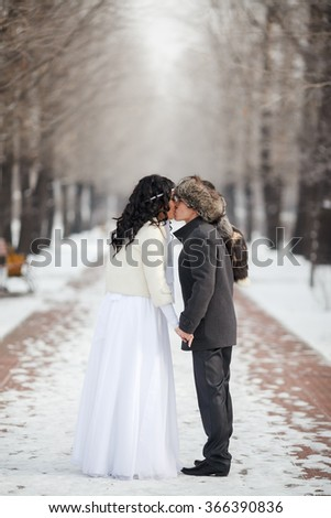 Asian bride and groom kissing in the middle of snowy winter alley. Young man in winter coat and fur hat, bride in white wedding dress with sheepskin. Cold season warmed wedding dresses, wedding coat. - stock photo