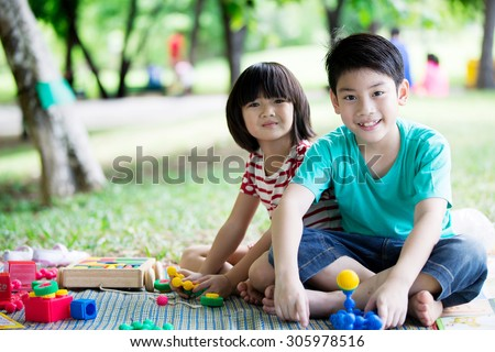 Asian  brother and sister having fun in the park , two cheerful children sitting on green grass, - stock photo