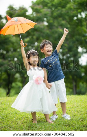 Asian  brother and sister having fun in the park , two cheerful children standing on green grass,