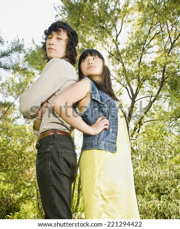 Asian brother and sister standing back to back - stock photo