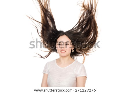 Asian brunette girl with long hair. Young attractive woman with hair in the air - stock photo