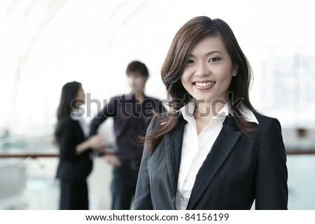 Asian Business colleagues standing in a row and smiling