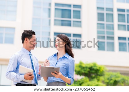 Asian business colleagues talking outdoors - stock photo