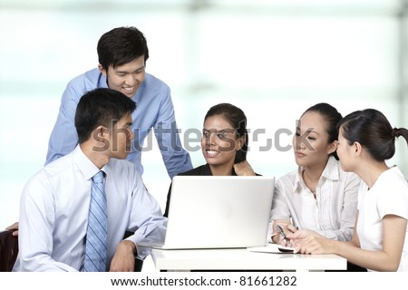 Asian business colleagues working around a laptop