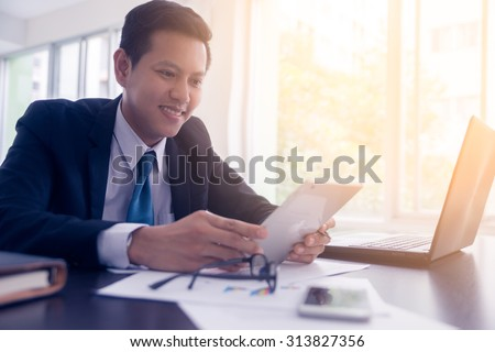 asian business executive working in office. - stock photo