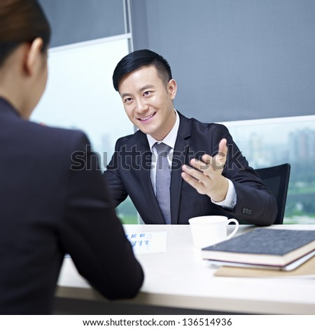 asian business executives discussing business in office. - stock photo