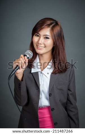 Asian business girl hold a microphone on gray background