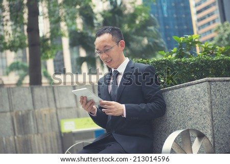 asian business male using portable computer on park in hong kong, vintage filter