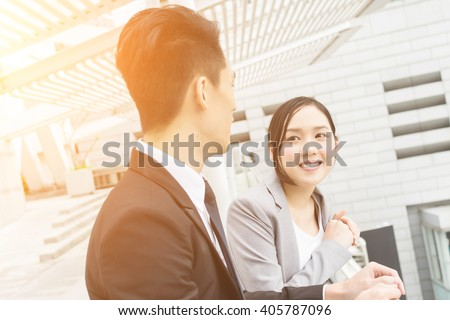 Asian business man and woman talk to each other - stock photo
