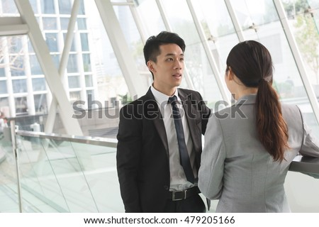 Asian business man and woman talk to each other