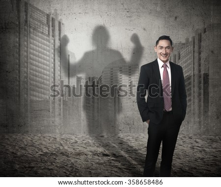 Asian business man casting a shadow of strength. Career concept - stock photo