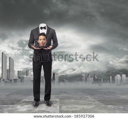 Asian business man doing a sacrifice, offering his head. Metaphor of labor exploitation