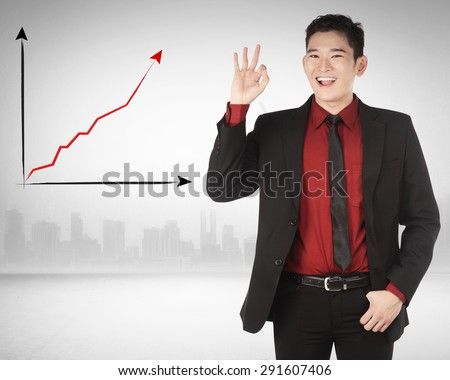 Asian business man give hand gesture OK with increase chart background