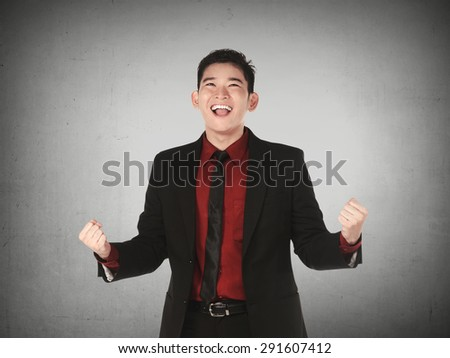 Asian business man happy over grey background - stock photo