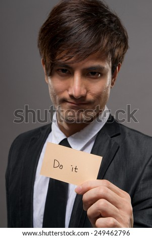 "Asian business man holding card writing ""do it"". - stock photo"