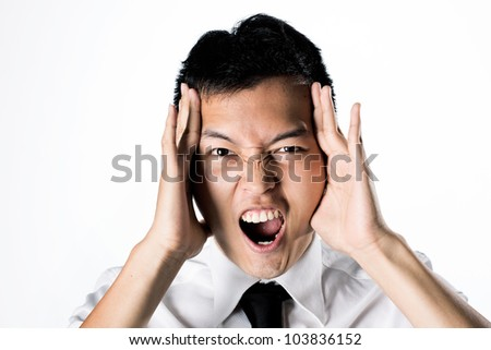 Asian business man holding his head and screaming.