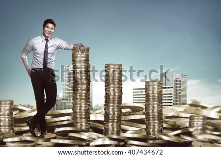 Asian business man leaning on the pile of coins. Business success concept - stock photo