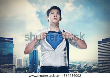 Asian business man open shirt like super hero. You can put your design on the shirt - stock photo