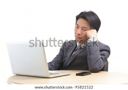 Asian business man resting in front of laptop isolated on white - stock photo