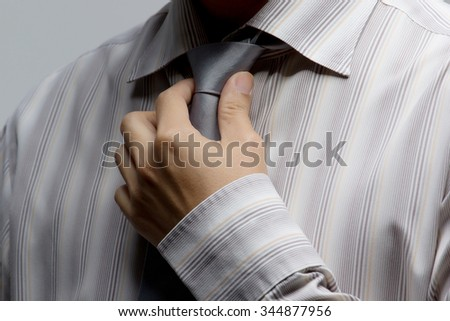 Asian business man shirt dressing up and adjusting tie on isolated - stock photo
