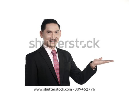 Asian business man show something isolated over white background - stock photo