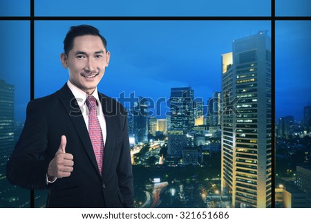 Asian business man show thumb up over night city background - stock photo
